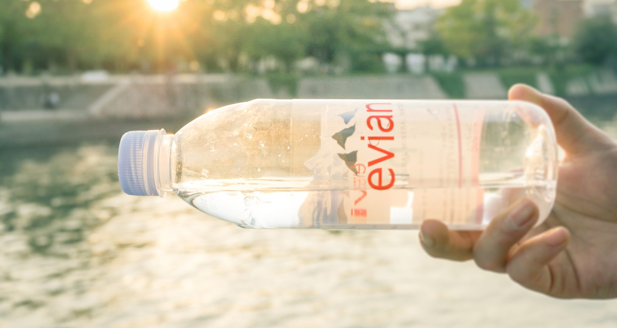 Evian bottled water being held by person