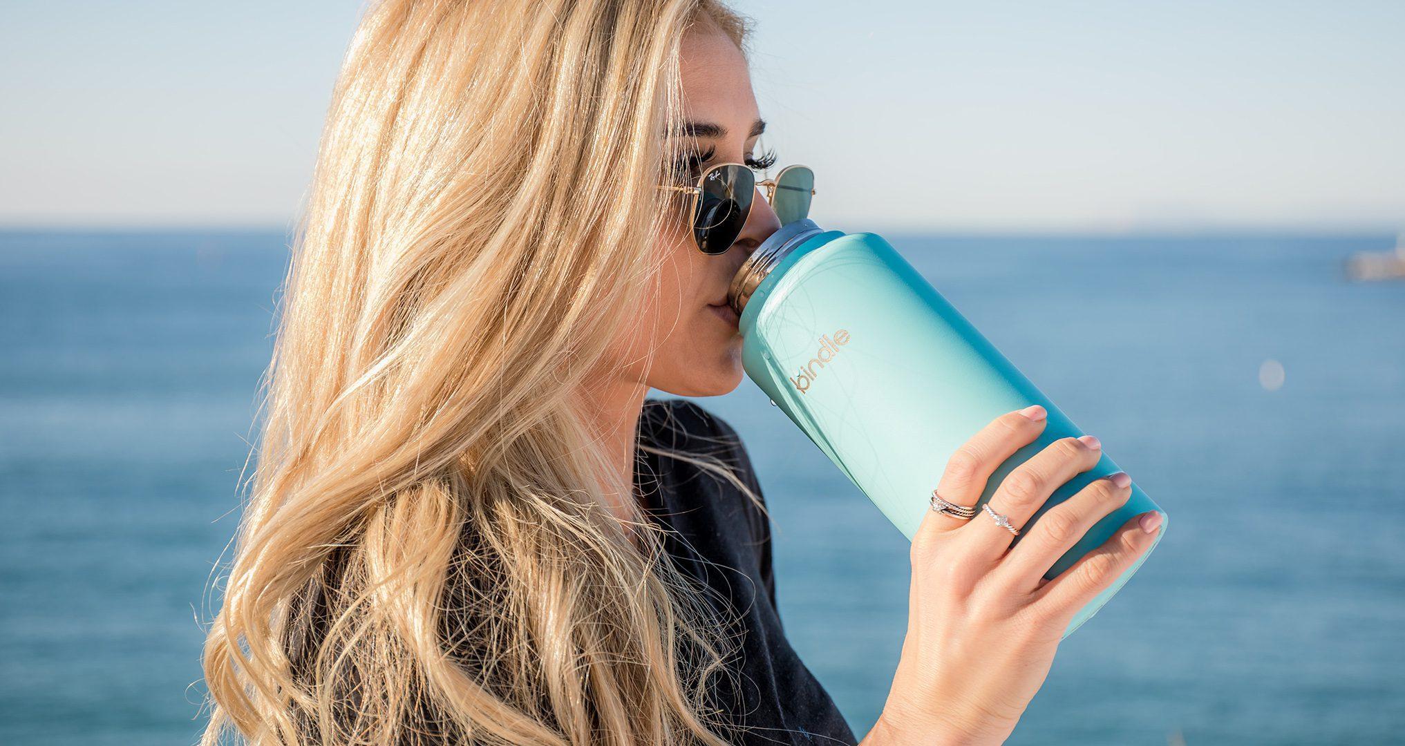 Woman drinking water near ocean