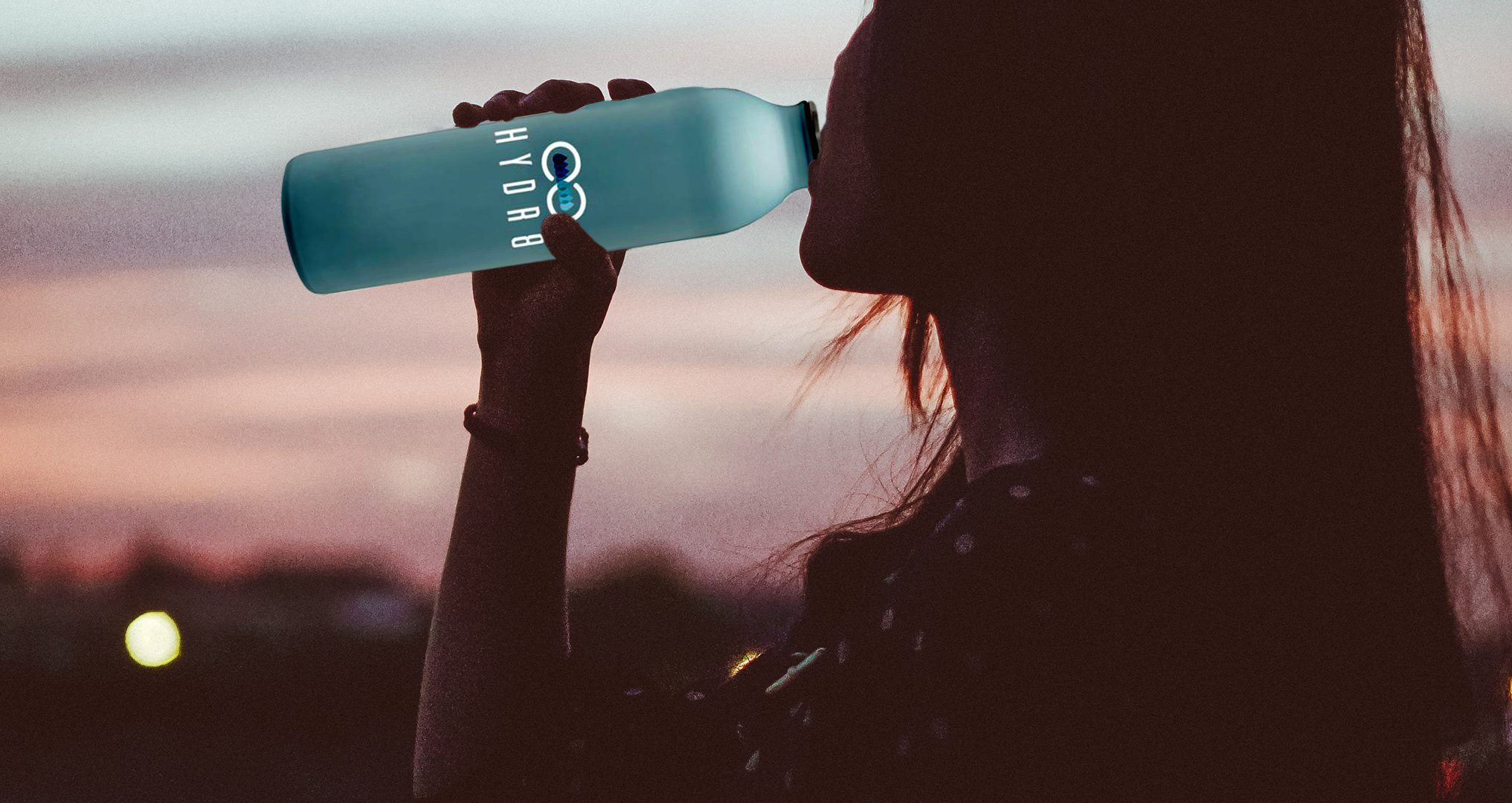 Woman drinking water out of a Hydr8 Hydroflask Bottle