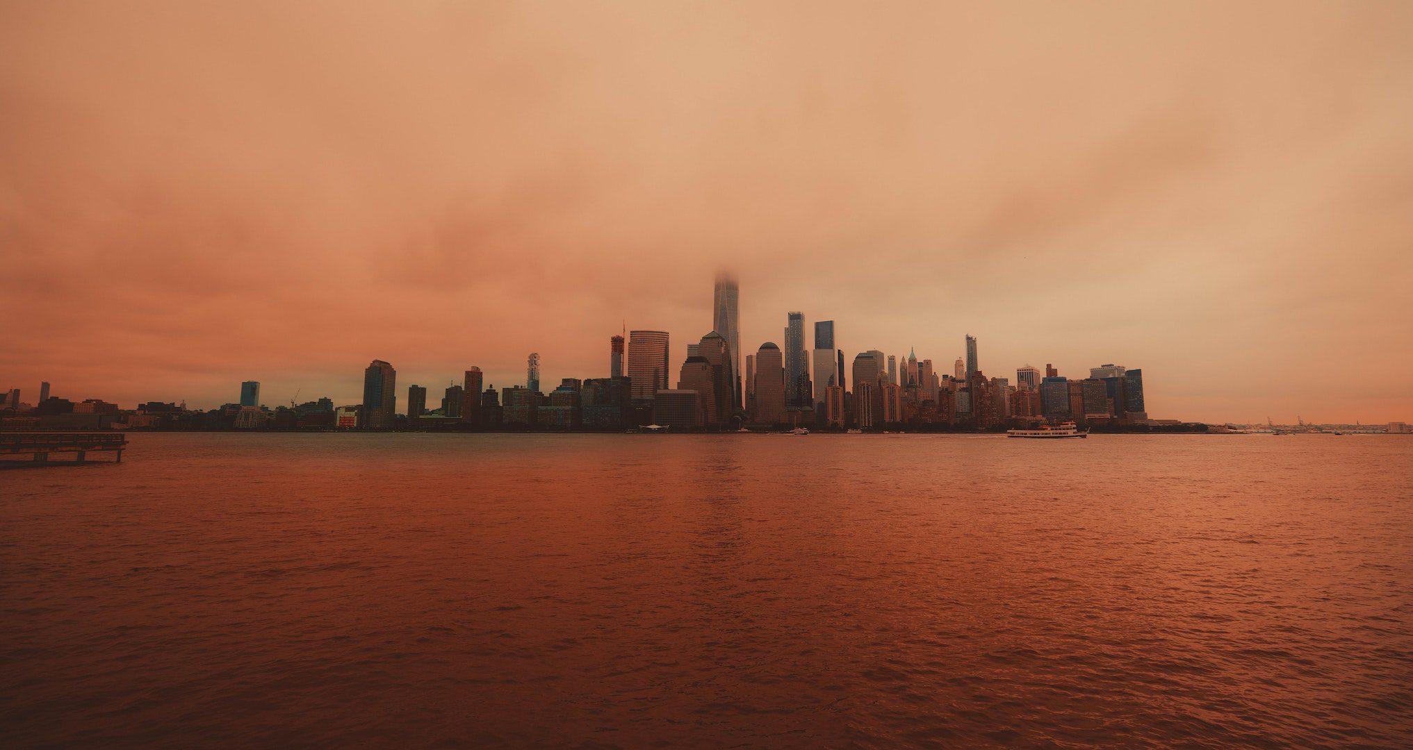 new york city skyline and harbor with orange sunset